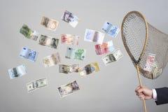 Hand, die Schmetterlings-Netz mit Fliegen-Banknoten hält Lizenzfreie Stockbilder