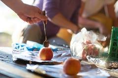 Hand, die Schokolade Chips Into Apple In Shed anfüllt Stockfoto
