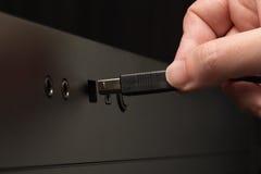 Hand, die schwarzen USB-Seilzug anhält Stockfoto