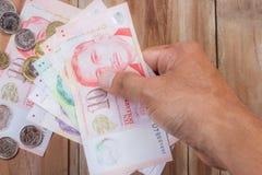 Hand, die Singapur-Geld auf Holztischhintergrund hält Stockfotos