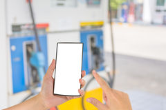 hand die slim telefoon en benzinestation op achtergrond houden Stock Afbeelding