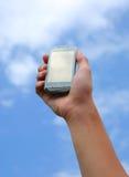 Hand die slimme telefoon in de hemel houdt Stock Afbeelding
