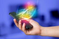 Hand die slimme telefoon met abstracte gloeiende lijnen houden Stock Foto