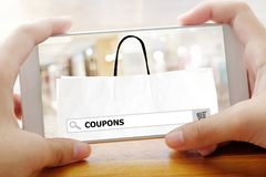 Hand die slimme telefoon met coupons op het scherm van de onderzoeksbar backg houden Stock Afbeelding