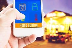 Hand die slimme telefoon met de toepassing van de huiscontrole met onduidelijk beeld houden Stock Foto's