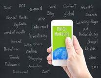 Hand die slimme telefoon met Digitaal Marketing woord en woord ab houden stock afbeelding