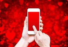 Hand die slimme telefoon met het zwarte rode scherm op rood hart houden boke Stock Foto's