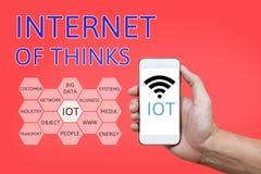 Hand die slimme telefoon met Internet van dingen & x28 houden; IoT& x29; woord en Royalty-vrije Stock Afbeeldingen