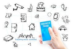 Hand die slimme telefoon met Internet van dingen (IoT) houden woord en Stock Fotografie