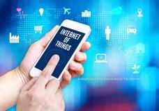 Hand die slimme telefoon met Internet van het woord van dingeniot houden en Stock Afbeelding
