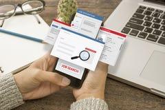 Hand die slimme telefoon met Job Search-Webhomepage met behulp van op het scherm stock afbeeldingen