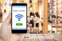 Hand die slimme telefoon met mobiele betaling houden en www onderzoeksbar Royalty-vrije Stock Foto's