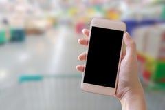 Hand die slimme telefoon met onduidelijk beeldachtergrond houden stock afbeeldingen
