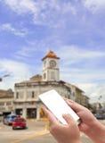 Hand die slimme telefoon op de stad houden royalty-vrije stock afbeelding