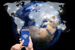 Hand die slimme telefoon op het netwerk van de wereldkaart en draadloze commu houden Stock Afbeelding
