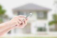 Hand die slimme telefoon op huisachtergrond houden Stock Fotografie