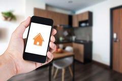 Hand die smartphone gebruiken door app slim huis op mobiel royalty-vrije stock afbeeldingen