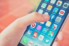 Hand die Smartphone houden terwijl wat betreft het Pictogram van Facebook App Stock Afbeeldingen