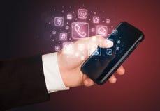 Hand, die Smartphone mit beweglichen APP-Ikonen hält Lizenzfreies Stockbild