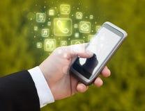 Hand, die Smartphone mit beweglichen APP-Ikonen hält Lizenzfreie Stockbilder