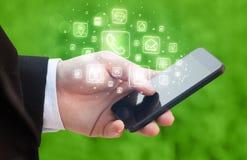 Hand, die Smartphone mit beweglichen APP-Ikonen hält Stockfoto