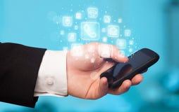 Hand, die Smartphone mit beweglichen APP-Ikonen hält Stockbild
