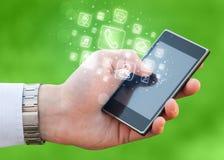 Hand, die Smartphone mit beweglichen APP-Ikonen hält Stockfotos