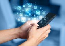 Hand, die Smartphone mit beweglichen APP-Ikonen hält Stockfotografie