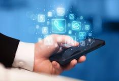 Hand, die Smartphone mit beweglichen APP-Ikonen hält Lizenzfreie Stockfotos