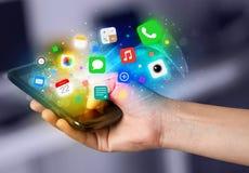 Hand, die Smartphone mit bunten APP-Ikonen hält Stockfotos