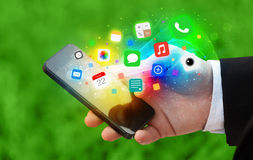 Hand, die Smartphone mit bunten APP-Ikonen hält Lizenzfreie Stockbilder