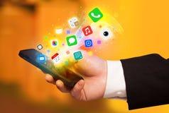 Hand, die Smartphone mit bunten APP-Ikonen hält Stockbild