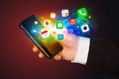 Hand, die Smartphone mit bunten APP-Ikonen hält Stockfoto