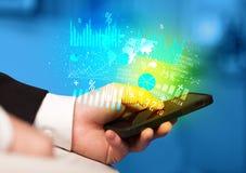 Hand, die Smartphone mit Geschäftsdiagrammen hält Stockbilder