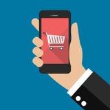 Hand, die Smartphone mit Warenkorbikone hält Stockbild