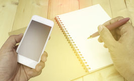 Hand die smartphone op boekachtergrond houden Royalty-vrije Stock Foto's