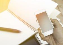 Hand die smartphone op vage boekachtergrond houden Royalty-vrije Stock Afbeeldingen