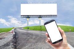 Hand die smartphone op Wegenkromme houden met groen grasblauw Stock Foto's