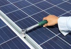 Hand, die Sonnenkollektor-Klammer mit Drehmoment-Schlüssel festzieht Lizenzfreie Stockbilder