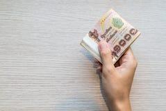 Hand, die Stapel von tausend thailändischem Geld des Bades gibt stockbild