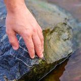 Hand die steen bij het stapelen van stenen op de rivieroever zetten De stenen worden gestapeld aan de rivierkant stock afbeelding