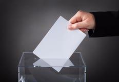 Hand, die Stimmzettel in Kasten einsetzt Stockfotos