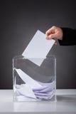 Hand, die Stimmzettel in Kasten einsetzt Stockfotografie