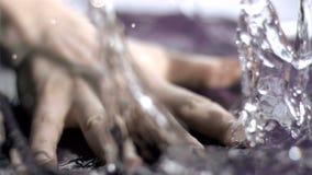 Hand die in super langzame motie de oppervlakte van water slaan stock footage