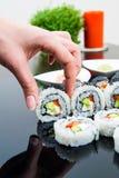 Hand, die Sushi auf schwarzem Hintergrund anhält Lizenzfreies Stockbild