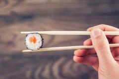 Hand, die Sushirolle unter Verwendung der Essstäbchen hält Stockfotografie
