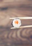 Hand, die Sushirolle unter Verwendung der Essstäbchen hält Stockfoto