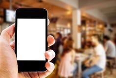Hand, die Telefon auf Caféhintergrund hält Lizenzfreie Stockfotografie