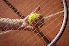 Hand, die Tennisball durch Schlägerschnur hält Lizenzfreie Stockbilder