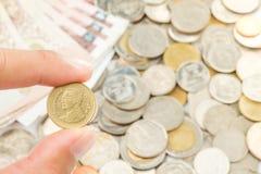Hand, die Thailand zwei Bahtmünzen hält Lizenzfreies Stockbild